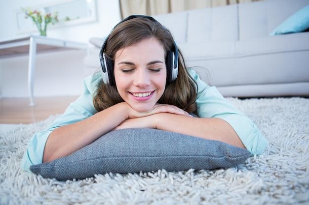 Vreedzame vrouw luisteren mijmeren op de vloer liggen
