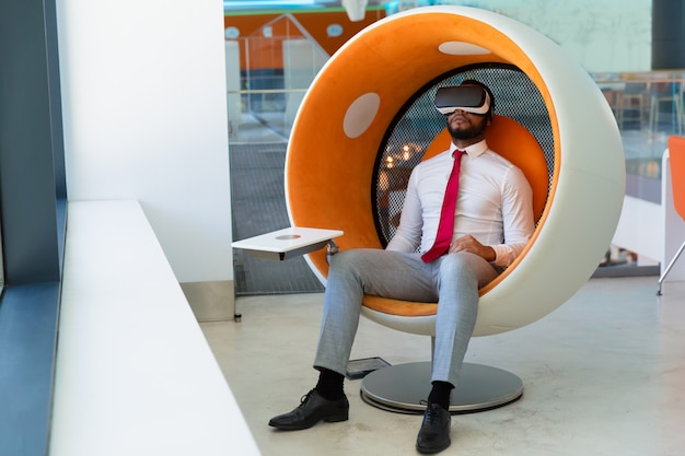 Vreedzame zakenman die in vr-hoofdtelefoon van virtuele video genieten
