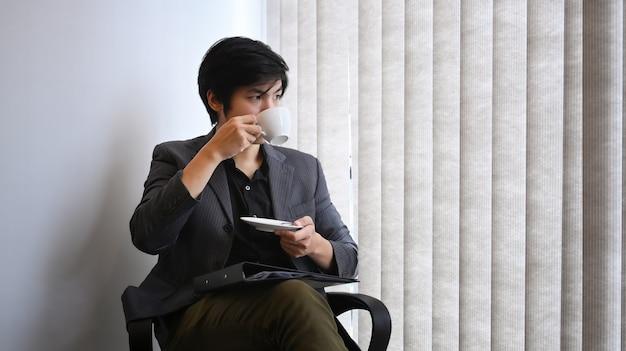Vreedzame zakenman die 's ochtends koffie drinkt op kantoor.