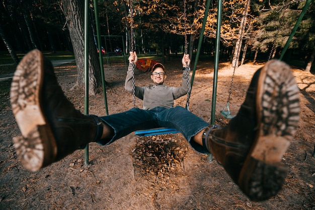 Vreemd bizar excentriek mensenconcept. volwassen mens in uitstekende modieuze laarzen die schommeling in stadspark berijden op speelplaats voor kinderen. benen wijd gespreid