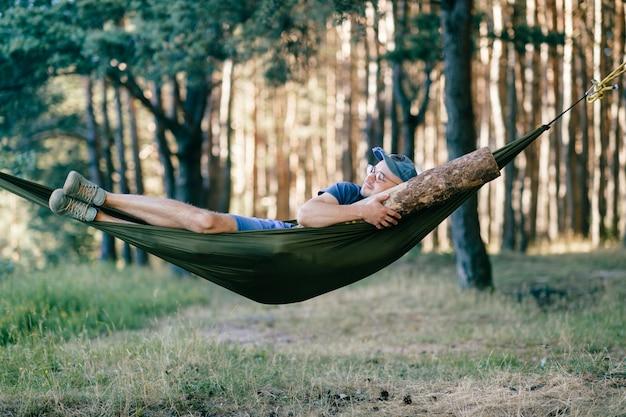 Vreemd raar vreemd ongebruikelijk mannelijk persoon. vreemde grappige gekke dwaze mensenslaap in hangmat met reusachtig houten logboek bij aard onder bomen. met balk in bed.