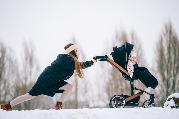 Vreemde bizzare jonge mooie moeder wandelwagen met haar dochtertje duwen door sneeuwbanken in de winter. moederschap moeilijkheden.