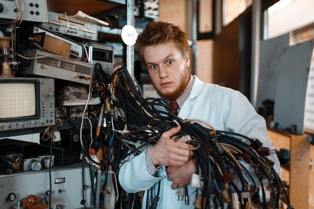 Vreemde ingenieur houdt stelletje draden met verschillende stekkers in laboratorium.