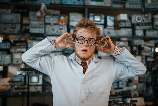 Vreemde ingenieur met elektrische lampen in zijn oren, test in laboratorium.