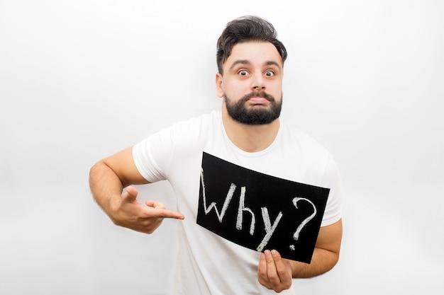 Vreemde jonge man toont emotie op gezicht en kijken. hij houdt plakkaat met geschreven woord waarom. ook wijst hij erop.