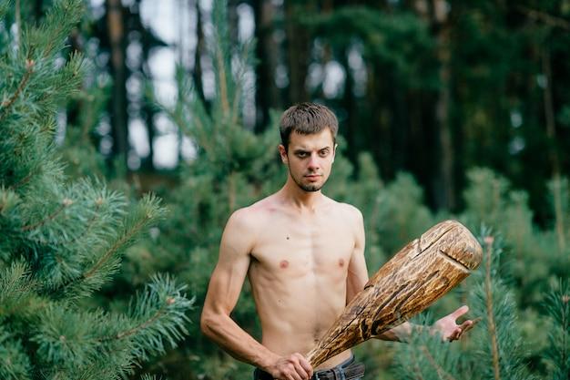 Vreemde primitieve naakte man met enorme houten stokjacht in bos. volwassen mannen hebben plezier als een gekke psyche met een onbeleefde club in handen. expressief opgewonden jongensgezicht. wilde mannelijke kracht. wrede krijger
