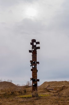 Vreemde roestige pijp steekt uit in het midden van een woestenij, die lijkt op een totempaal