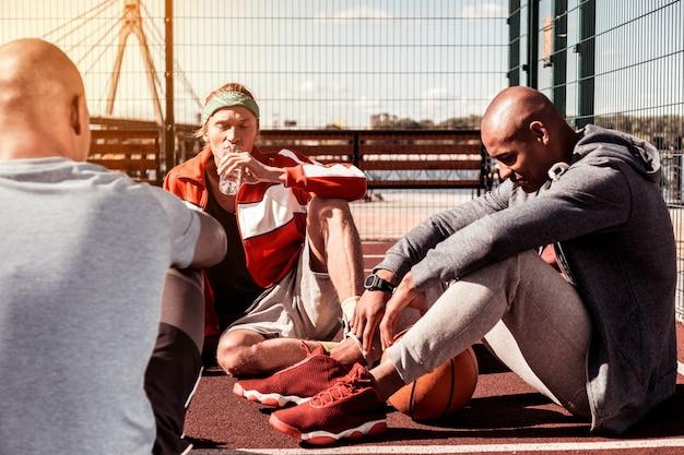 Vreselijk moe. aangename knappe mannen zittend op de grond terwijl ze samen uitrusten na de basketbalwedstrijd