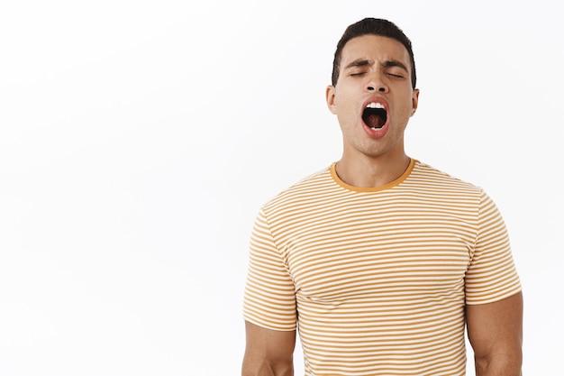 Vreselijk moe. aantrekkelijke jonge mannelijke man in gestreept t-shirt-