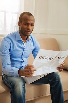 Vreselijk nieuws. geconcentreerde verbijsterde afro-amerikaanse man die een krant vasthoudt en leest terwijl hij op de bank zit