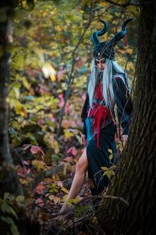Vreselijke vrouw met hoorns en geweldige make-up in de buurt van de boom in het bos
