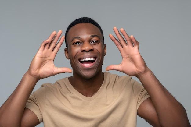 Vreugde, emotie. vrolijke donkere huid jonge man met brede glimlach met handen op gezichtsniveau staande op een grijze achtergrond