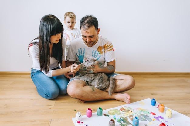 Vreugde familie kunst blij vader moeder en zoon tonen handen in felle kleuren verf samen foto art