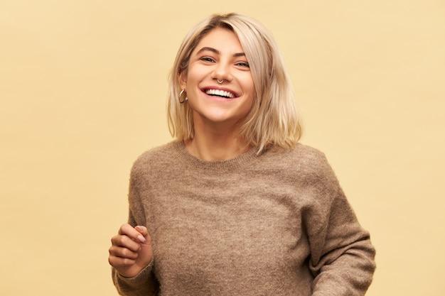 Vreugde, geluk en positieve emoties. portret van stijlvolle mooie jonge vrouw in gezellige trui met plezier, lachen om een goede grap, zich gelukkig en zorgeloos voelen, poseren geïsoleerd op de lege muur van de kopie ruimte