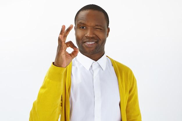 Vreugde, geluk en positiviteit concept. zelfverzekerde jonge donkere mannelijke werknemer die bereidheid uitdrukt om de taak te voltooien, ok gebaar toont en vrolijk lacht naar de camera, poseren in studiomuur