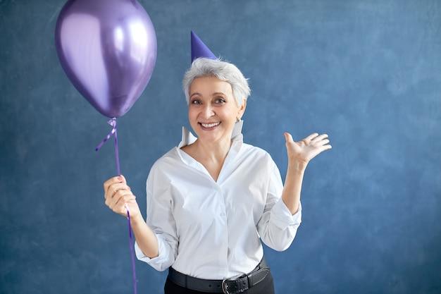 Vreugde, geluk, plezier en positieve emoties concept. portret van mooie opgewonden 50-jarige grijze haren vrouw met conische hoed op haar hoofd