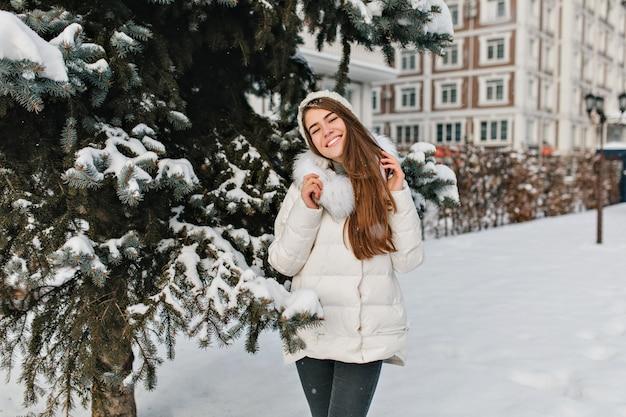 Vreugde, geluk van geweldig mooi meisje glimlachend in warme winterkleren op vr boom vol met sneeuwruimte.