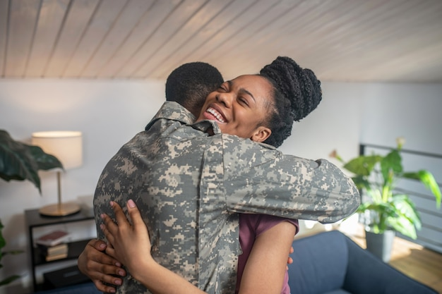 Vreugde van ontmoeting. vrolijke jonge vrouw met een donkere huid die met gesloten ogen een militaire man knuffelt die thuis met de rug naar de camera staat