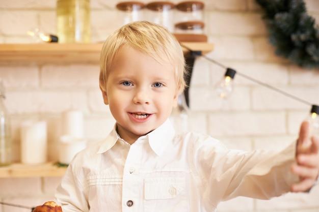 Vreugde, vrije tijd en positieve emoties. portret van emotionele schattige kleine jongen in wit overhemd gebaren actief honger hebben, snack voor de lunch, iets zeggen, poseren in gezellige keuken