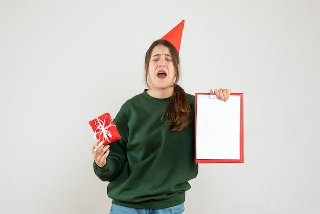 Vreugdeloos meisje met feestmuts huilen terwijl documenten en cadeau op wit