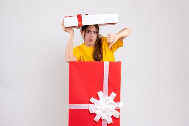 Vreugdeloos meisje met kerstmuts maken duim omlaag teken achter grote xmas gift op wit