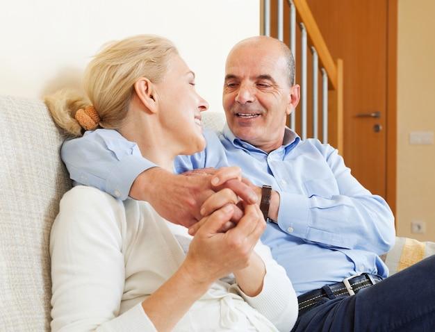 Vreugdevolle bejaarde echtpaar samen op de sofa in interieur