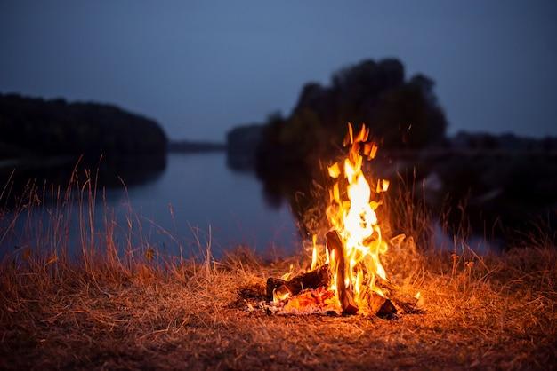 Vreugdevuur aan de oever van de rivier in de avond. sfeervolle foto van een kampvuur bij de rivier