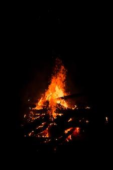 Vreugdevuur brandende bomen 's nachts. vreugdevuur dat helder brandt, warmte, licht, kamperen, groot vreugdevuur.