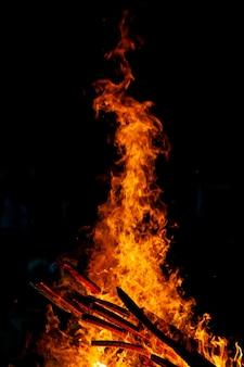 Vreugdevuur dat op een donkere achtergrond brandt, houtgestookte vlam.