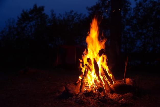 Vreugdevuur in het nachtbos. reizen, buitenactiviteiten, romantiek.