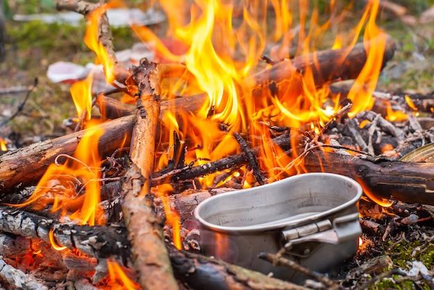 Vreugdevuur koken tijdens trektocht. koken in een bolhoed op het vuur in de natuur. stock foto
