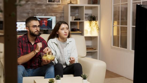 Vriend bedekt de ogen van zijn vriendin tijdens het kijken naar een horrorfilm op televisie.