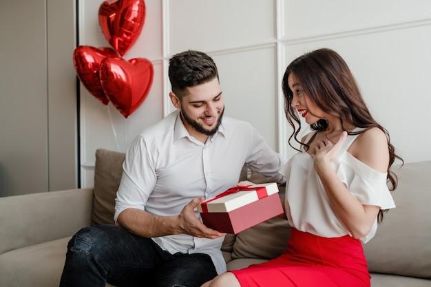 Vriend die gift in huidige doos geeft aan vriendin met hartvormige ballons op bank thuis