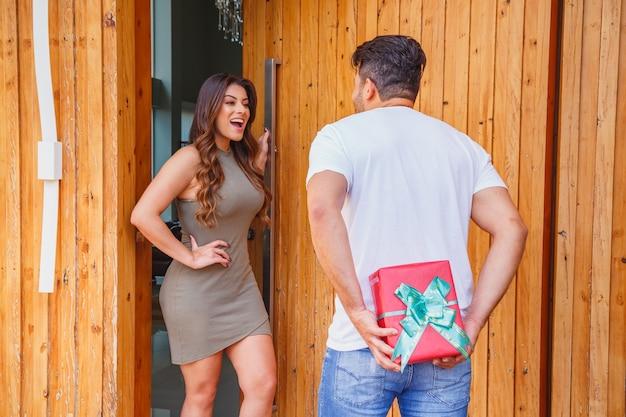 Vriend die zijn vriendin bezoekt en verrassing maakt met zijn handen achter het verbergen van het cadeau terwijl ze de deur voor hem opent om binnen te komen.