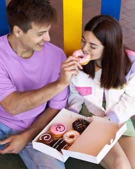 Vriend en vriendin die buiten donuts eten