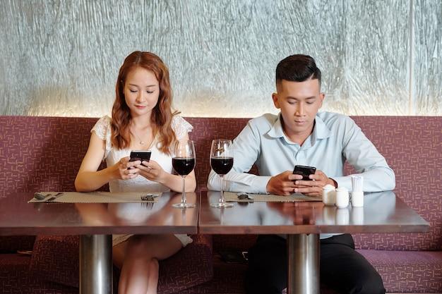 Vriend en vriendin drinken wijn, wachten op eten en checken social media op smartphones