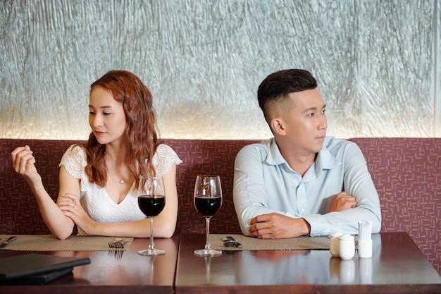 Vriend en vriendin kijken elkaar niet aan als ze aan een cafétafel zitten met wijnglazen, concept van relatieproblemen