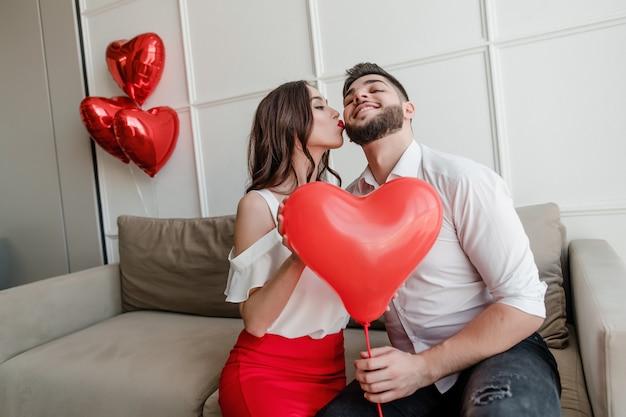 Vriend en vriendin met hartvormige ballon glimlachen en zittend op de bank thuis