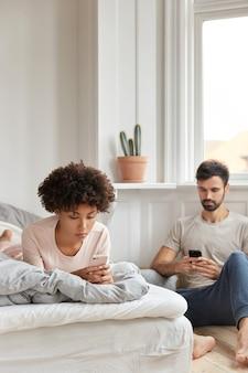 Vriend en vriendin van gemengd ras lezen een ontvangen melding, sturen sms terwijl ze in de slaapkamer rusten, negeren live communicatie, hebben ernstige uitdrukkingen, gericht op mobiel. verslaving en technologie