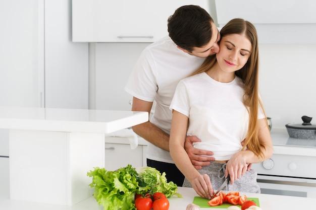 Vriend kussen meisje tijdens het koken