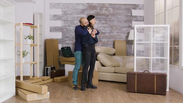 Vriend laat zijn vriendin hun nieuwe appartement zien. man knuffelen vrouw in nieuw appartement.