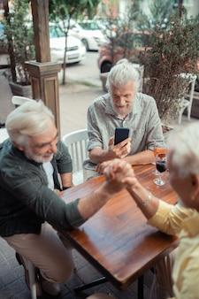 Vriend maakt video. bovenaanzicht van gepensioneerde mannen die armworstelen terwijl een vriend video maakt