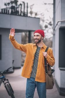 Vriend ontmoeten. jonge man in oranje jasje iemand ontmoeten en zijn hand zwaaien
