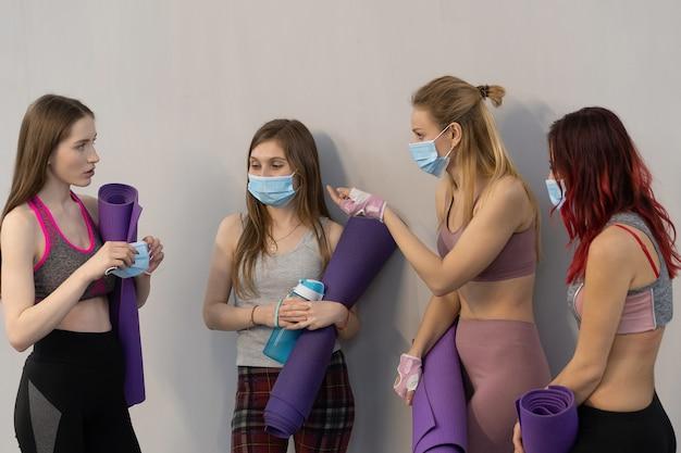 Vriend overtuigen om medisch gezicht beschermend masker te dragen atletische meisjes in sportoutfits staan naast de muur met een yogamat en praten met elkaar