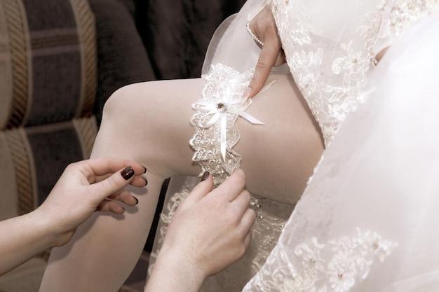 Vriend van de bruid draagt haar trouwkouseband. schoonheid en mode in dameskleding