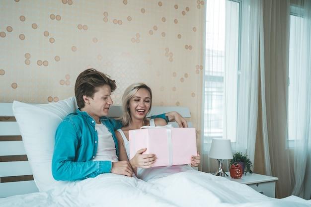 Vriend verras zijn vriendin met geschenkdoos op het bed