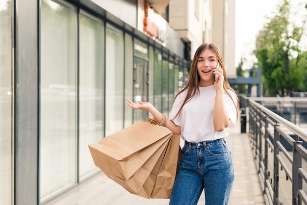 Vriend vertellen over verkoop. mooie jonge lachende vrouw met boodschappentassen en praten over de mobiele telefoon terwijl ze buiten staat