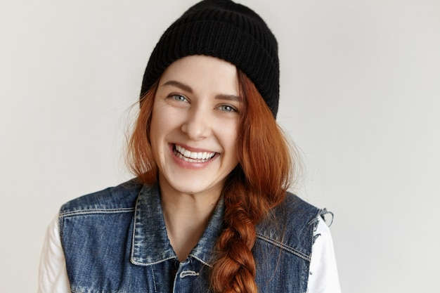 Vriendelijk charmant kaukasisch meisje met gemberhaar in vlecht, vrolijk lachend