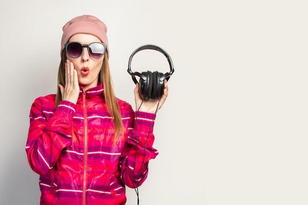 Vriendelijk emotioneel. jonge vrouw met bril, een hoed en een roze sportjasje houdt een koptelefoon