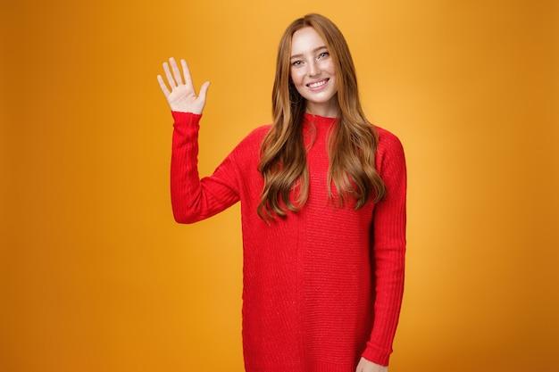 Vriendelijk en optimistisch goed uitziend gembermeisje in rode trui die palm opheft en naar de camera zwaait, hallo of hallo zegt, vrolijk glimlachend schattig, nieuwe leden begroetend die zich voordeed op oranje achtergrond